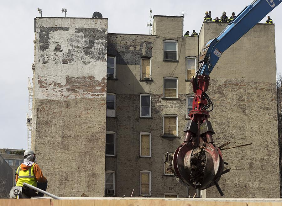 Construction workers cleanup damage from the East Village fire.