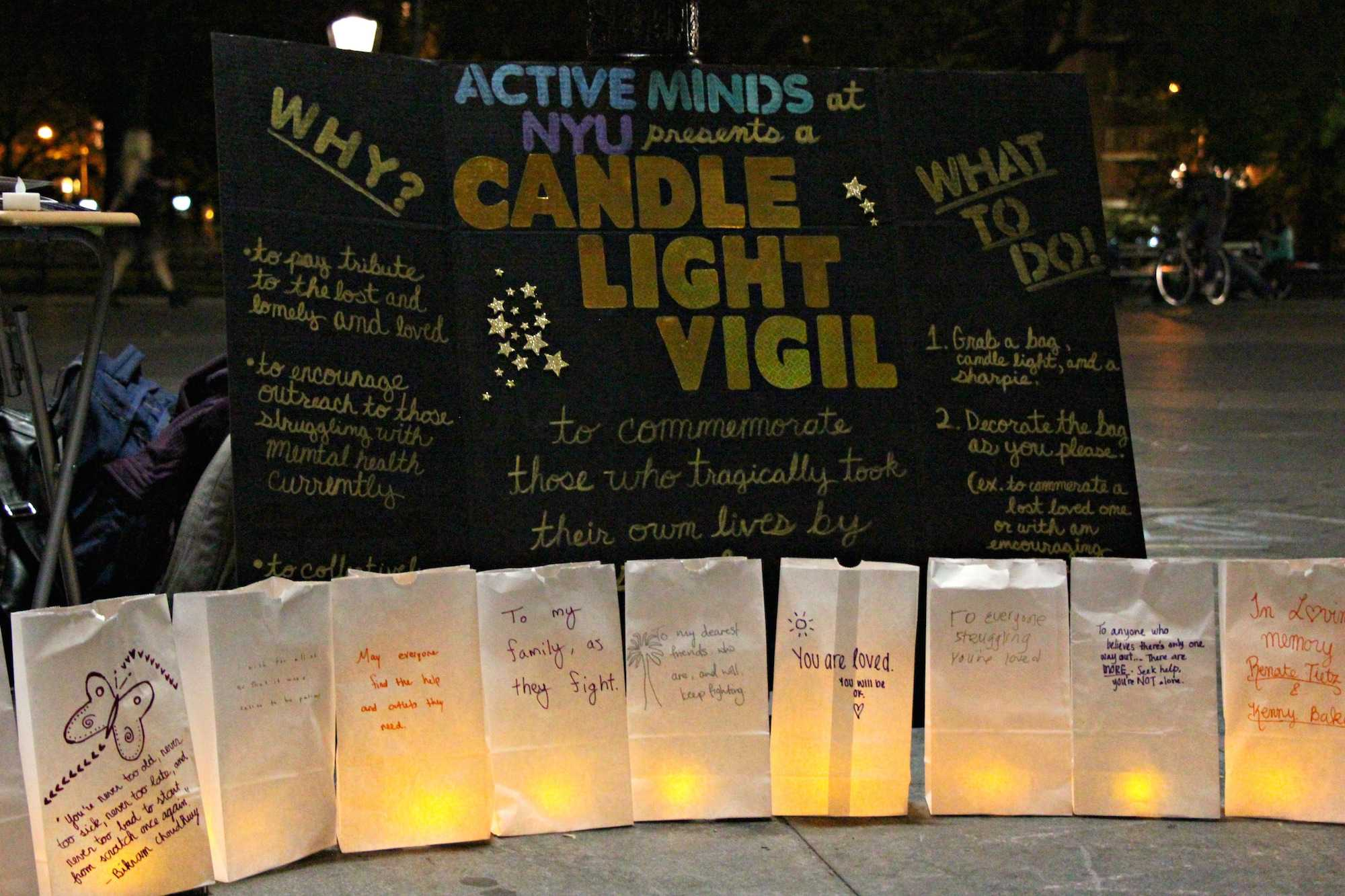 Posters and words of commemoration and encouragement as part of a candlelight vigil for those who have committed suicide.