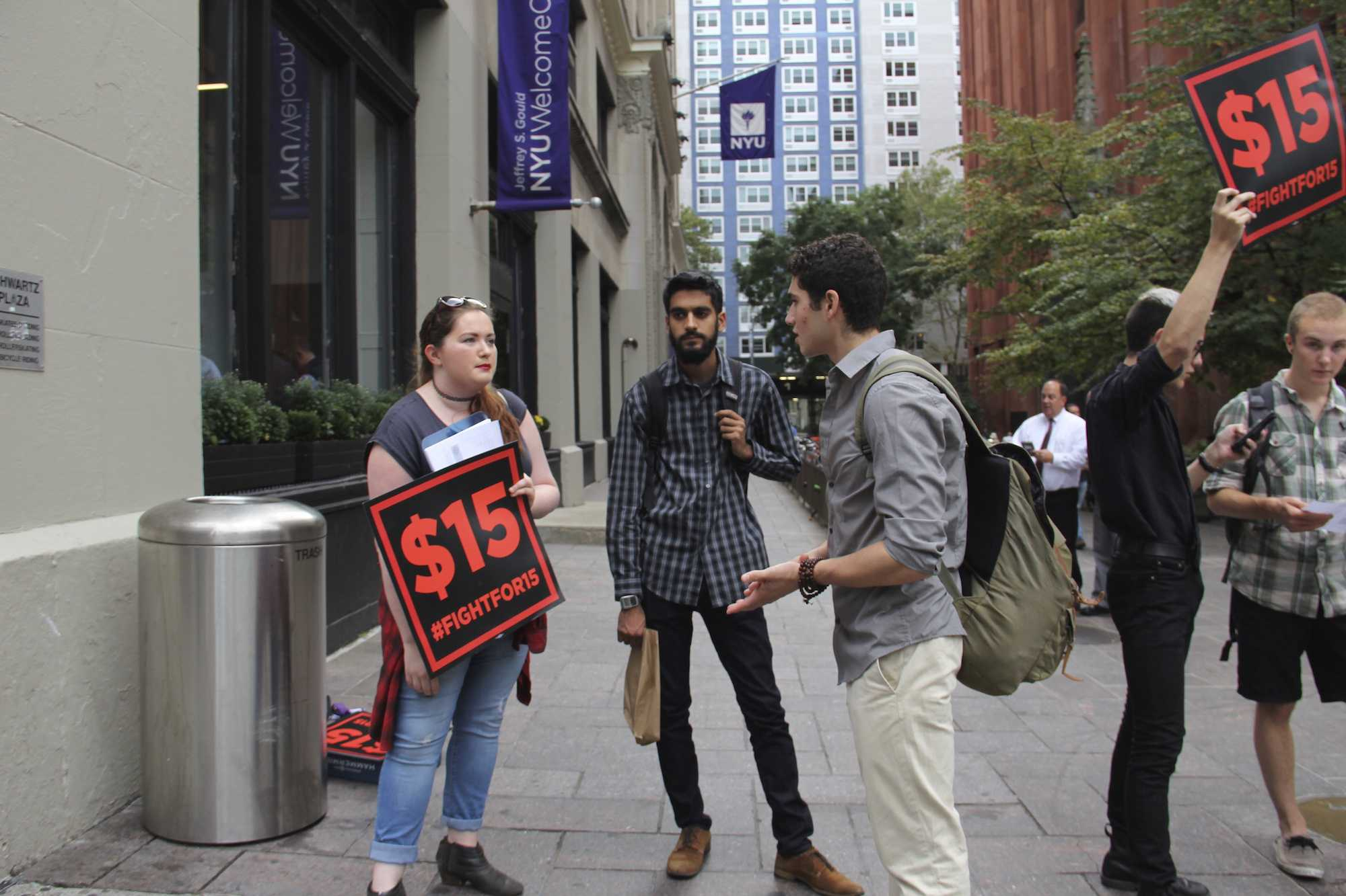 Haley Quinn (left) and Vishnu Bachani (center) of NYU's Student Labor Action Movement speak to prospective student Elliot Waxman (right) about raising student worker pay to $15 an hour in front of the NYU Welcome Center on Friday, Oct. 9, 2015.