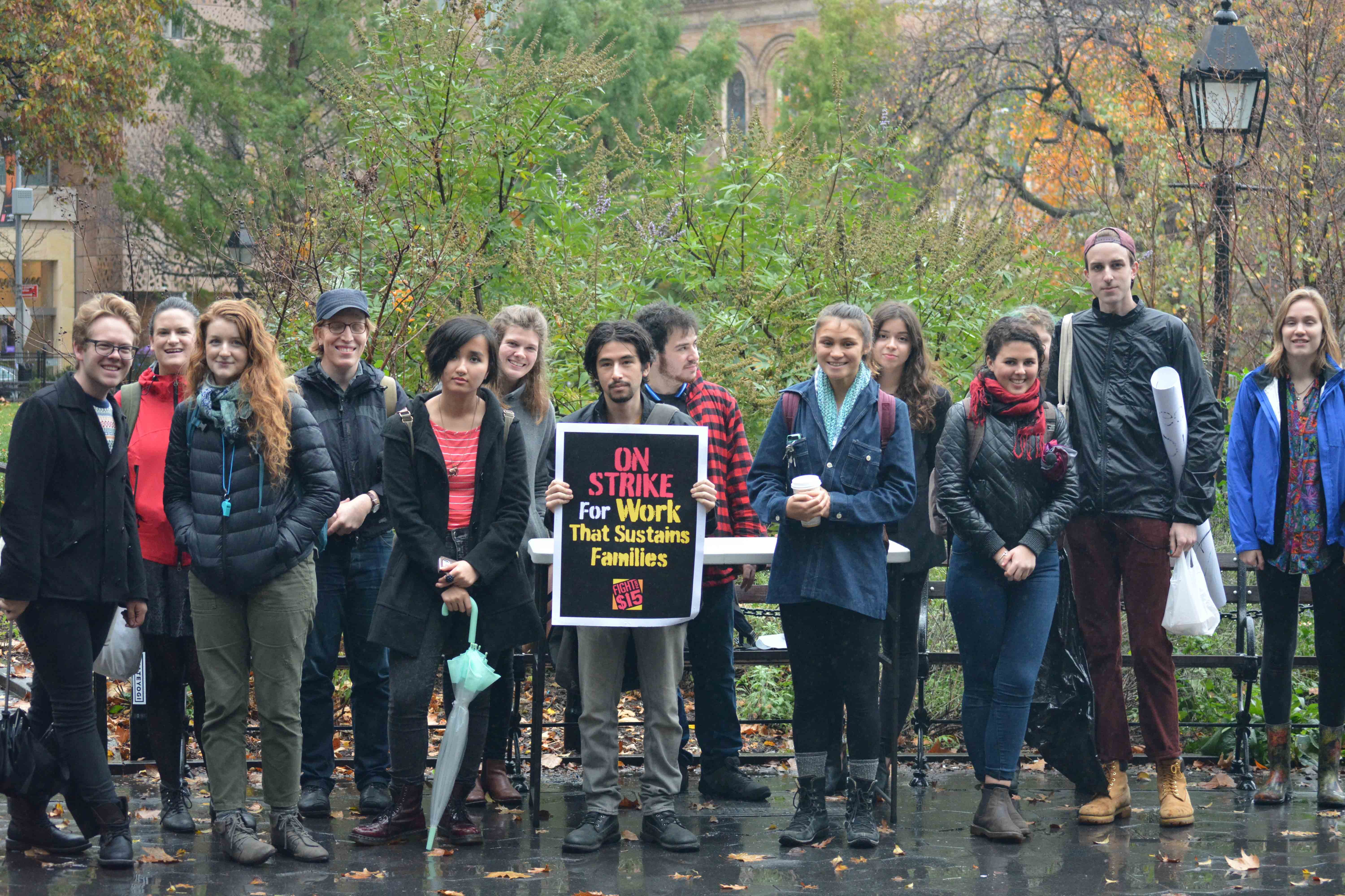 Braving the rain, students gather in Washington Square Park to protest wages provided by NYU for their student employees.