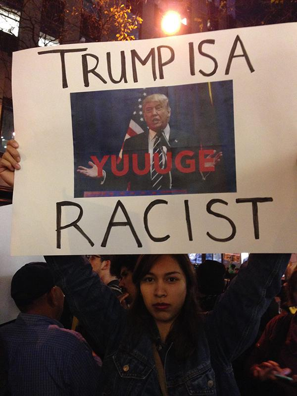 NYU+Dream+Team+protester+holds+a+sign+at+30+Rockefeller+Center+in+retaliation+to+Donald+Trump%E2%80%99s+appearance+on+Saturday+Night+Live.