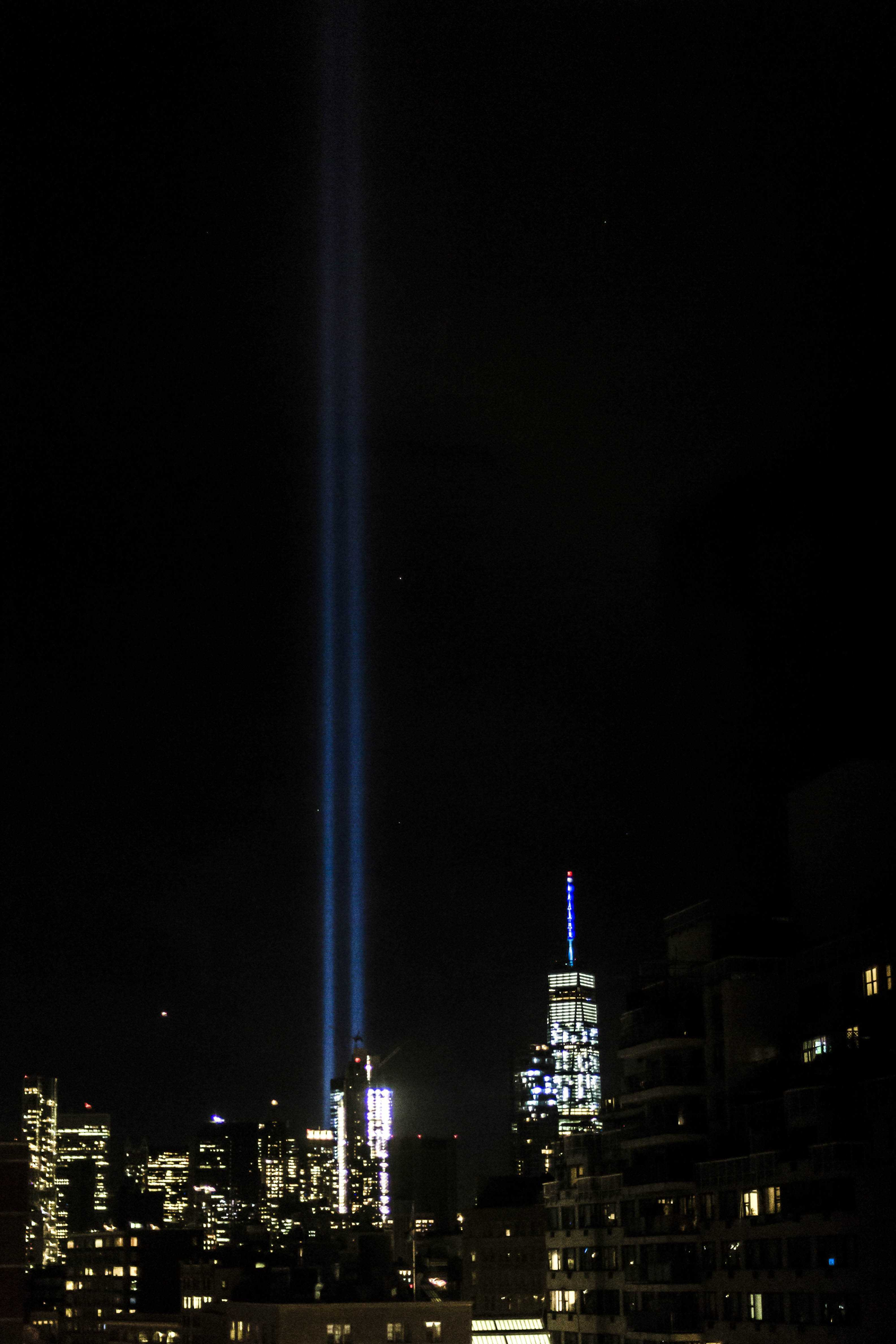 Two bright beams shine from the 9/11 Memorial's reflecting pools, marking the sky with a ghost of where the Twin Towers once stood.