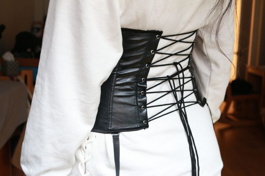 A+lace-up+faux-leather+corset+paired+with+a+white+hooded+sweatshirt.+Aspects+of+the+traditional+Victorian+style+corset+have+seen+a+revival+recently%2C+appearing+on+the+runways+of+brands+like+Giambattista+Valli.