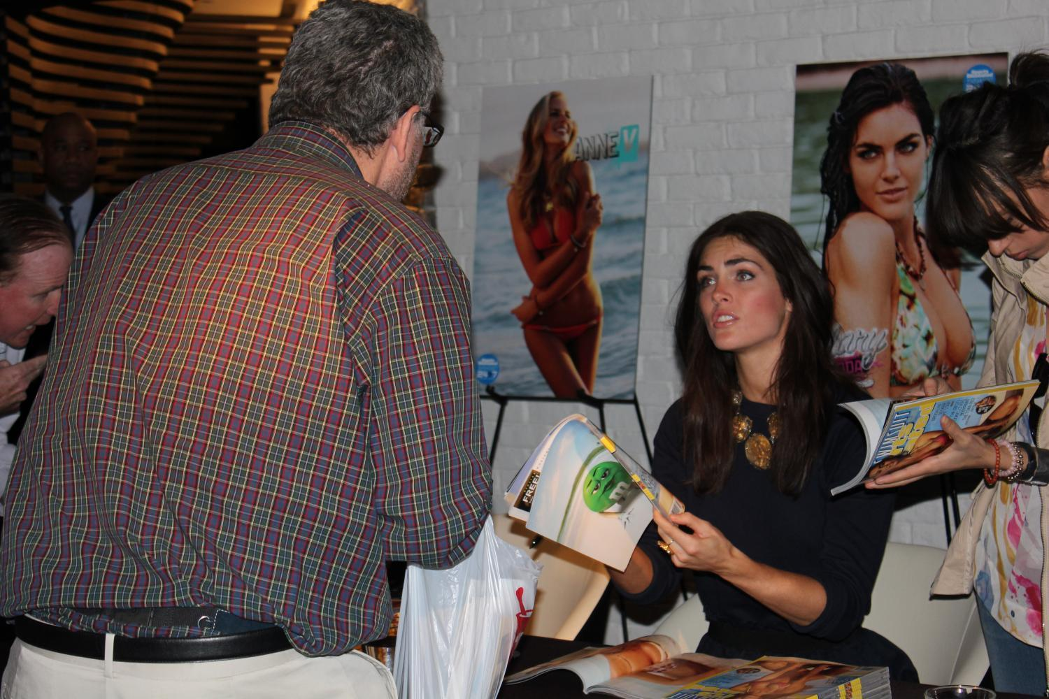 Model Hilary Rhoda signs a copy of the yearly Sports Illustrated swimsuit issue for a man at the Cosmopolitan of Las Vegas. Many people feel this issue promotes sexual objectification.