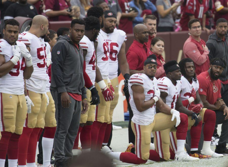 Various+NFL+players+have+knelt+during+the+playing+of+the+playing+of+the+national+anthem+to+protest+police+brutality+and+racial+violence.+Critics+have+labelled+these+players+as+anti-militaristic%2C+so+many+players+chose+to+stand+on+veterans+day+out+of+respect+to+the+military.
