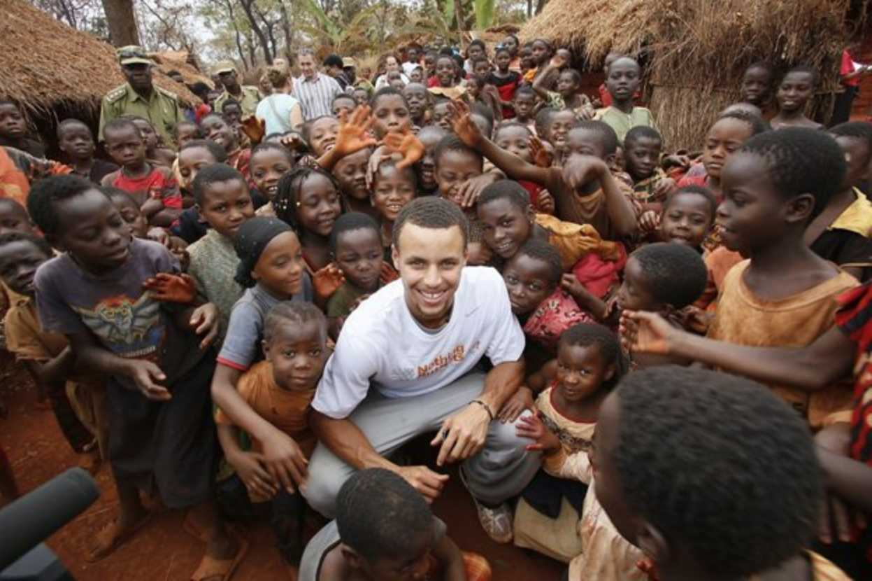 Golden State Warriors point guard Steph Curry with children at Nyarugusu Refugee Camp in Tanzania. Curry worked with Nothing But Nets, a charity that donates malaria-preventing nets to communities across Africa.