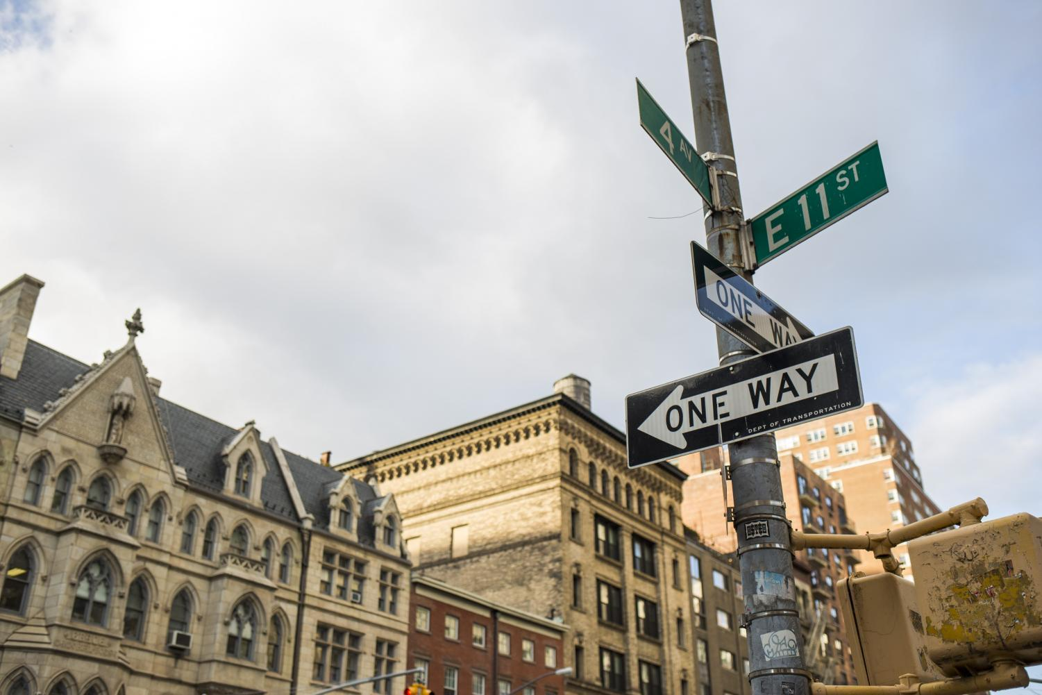 The street sign on the corner of 11th Street and Fourth Avenue.