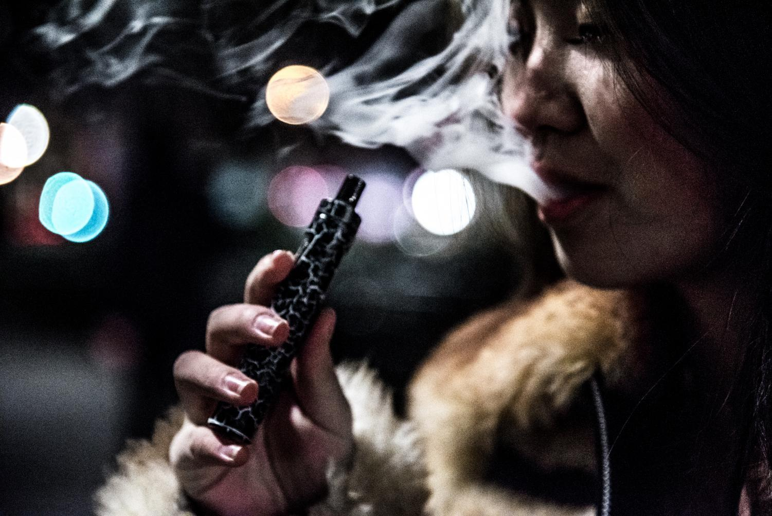 A first-year vapes in Union Square at night. She only started vaping since being at NYU, primarily doing so on nights out.