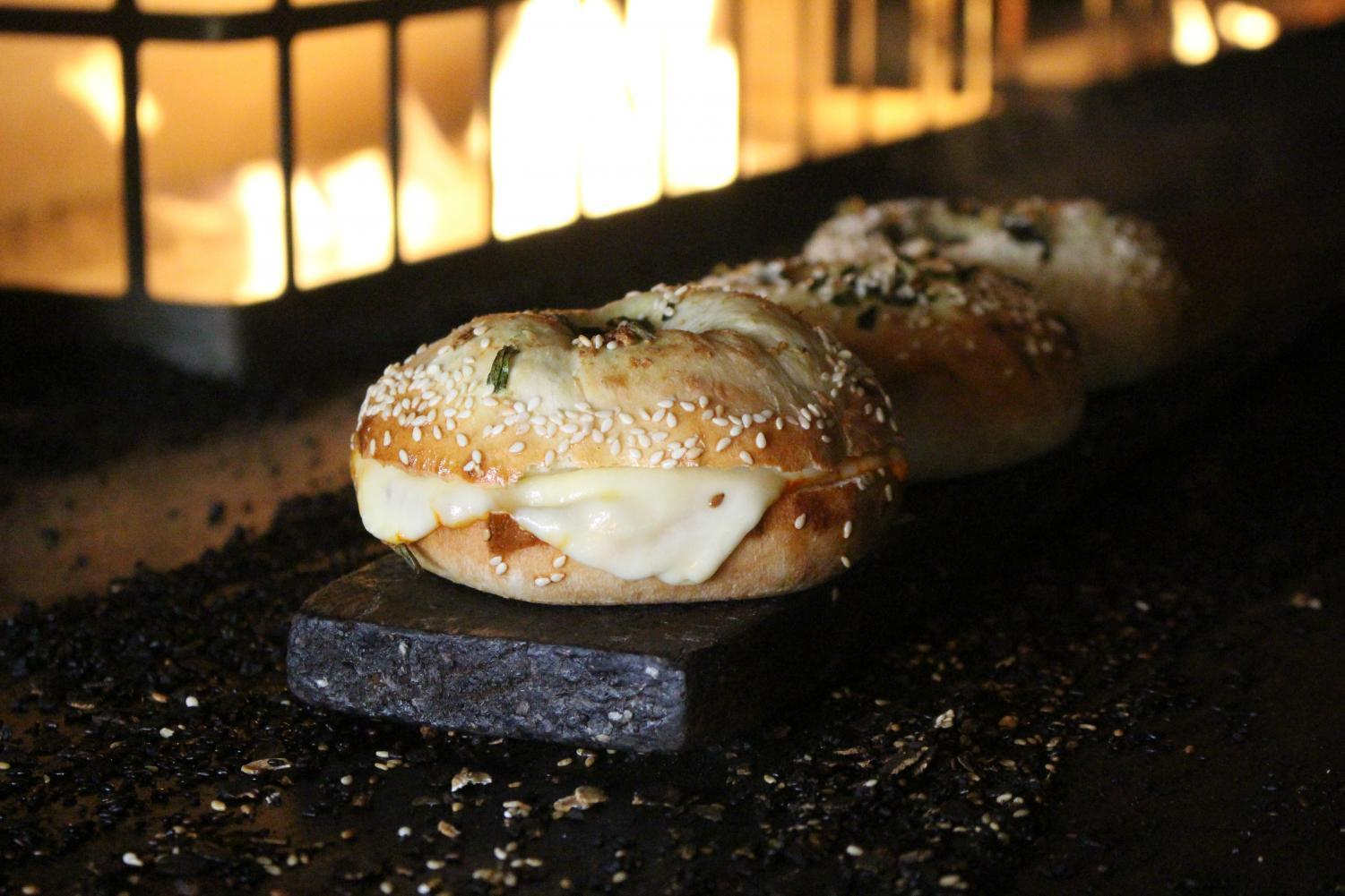 The new Don Angie x Black Seed collaboration bagel, a custom bialy topped and stuffed with green garlic, sesame, and different cheeses. This is part of Black Seed's ongoing monthly chef collaboration series.