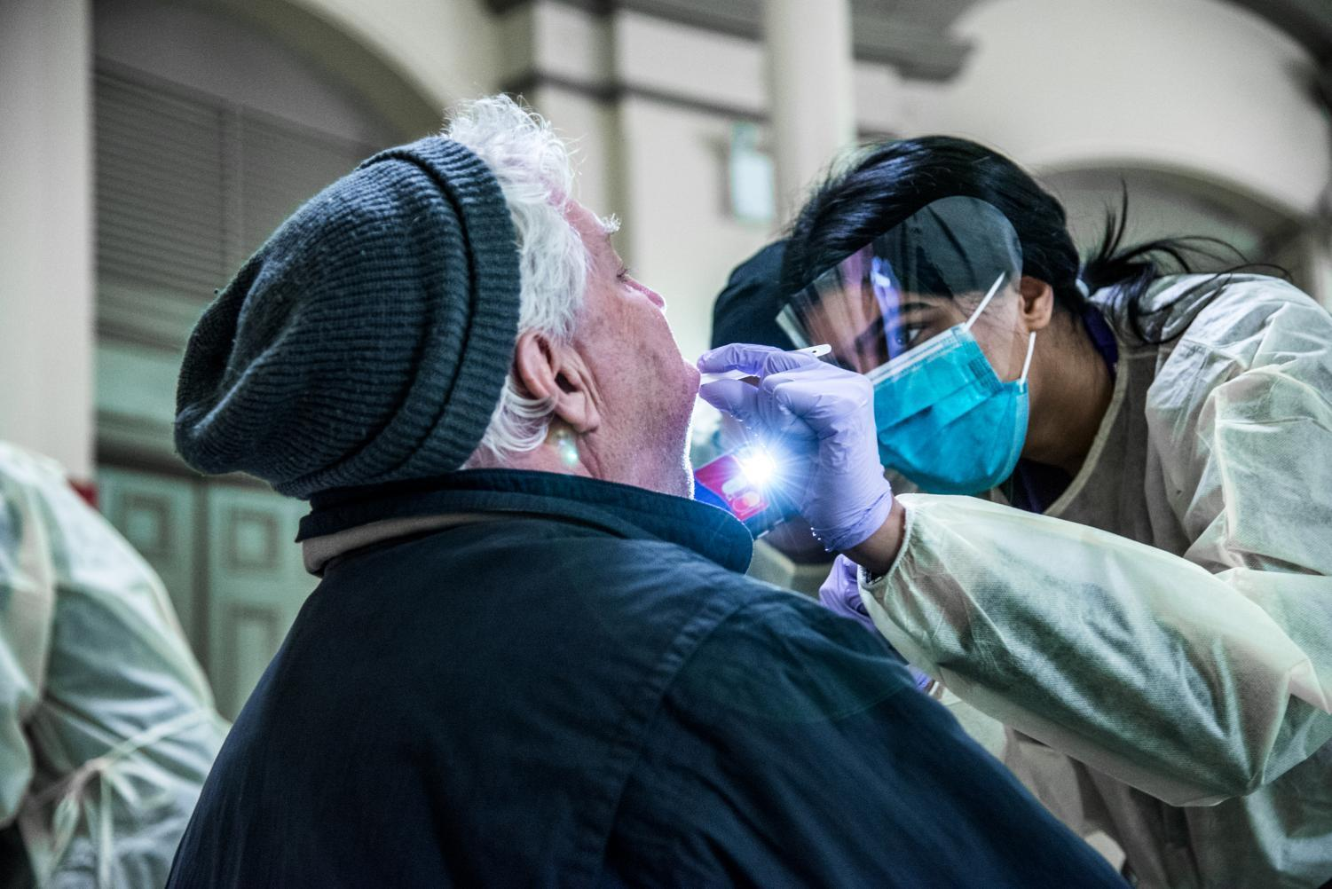 Second-year College of Dentistry student Amera Al-Faleh examines a patient's teeth at an outreach event, while another student shines a phone flashlight to give a better view.