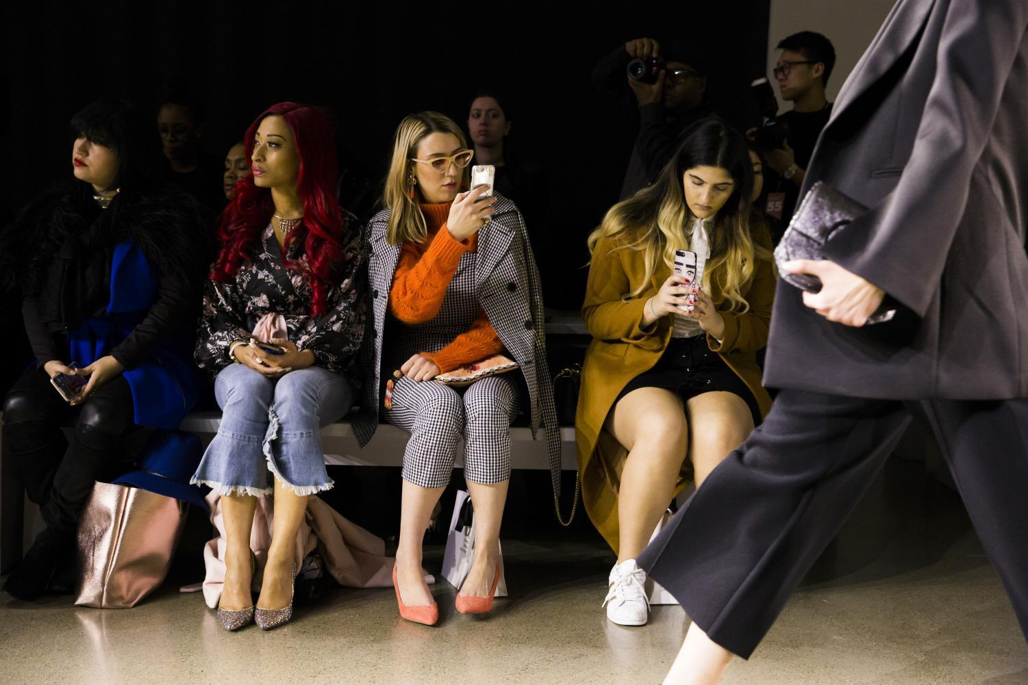 Audience members take photos and videos on their phones during the All Comes From Nothing FW18 show.