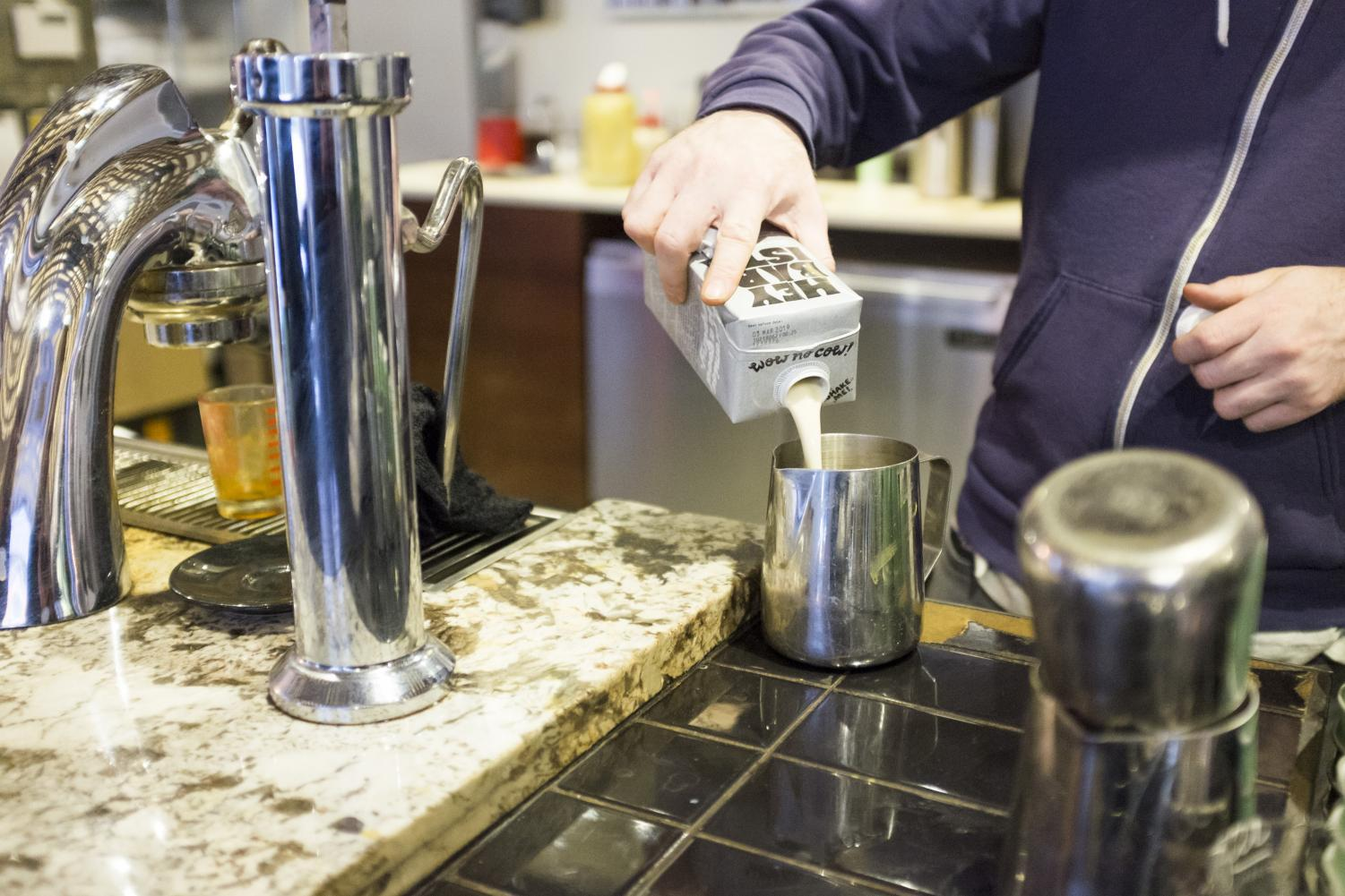 A barista pours Oatly oat milk at City of Saints on Astor Place.