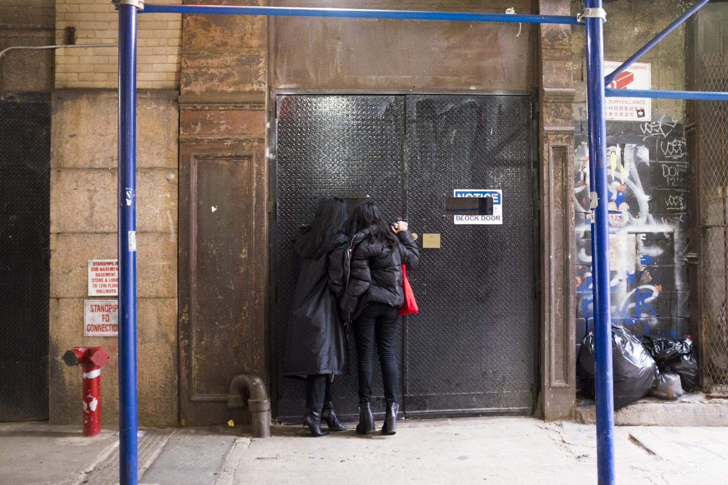 Two visitors peek inside Mmuseumm, located on Cortlandt Alley. Even when the museum is closed, visitors can call a toll-free number to hear about the objects, or look inside the building's windows.
