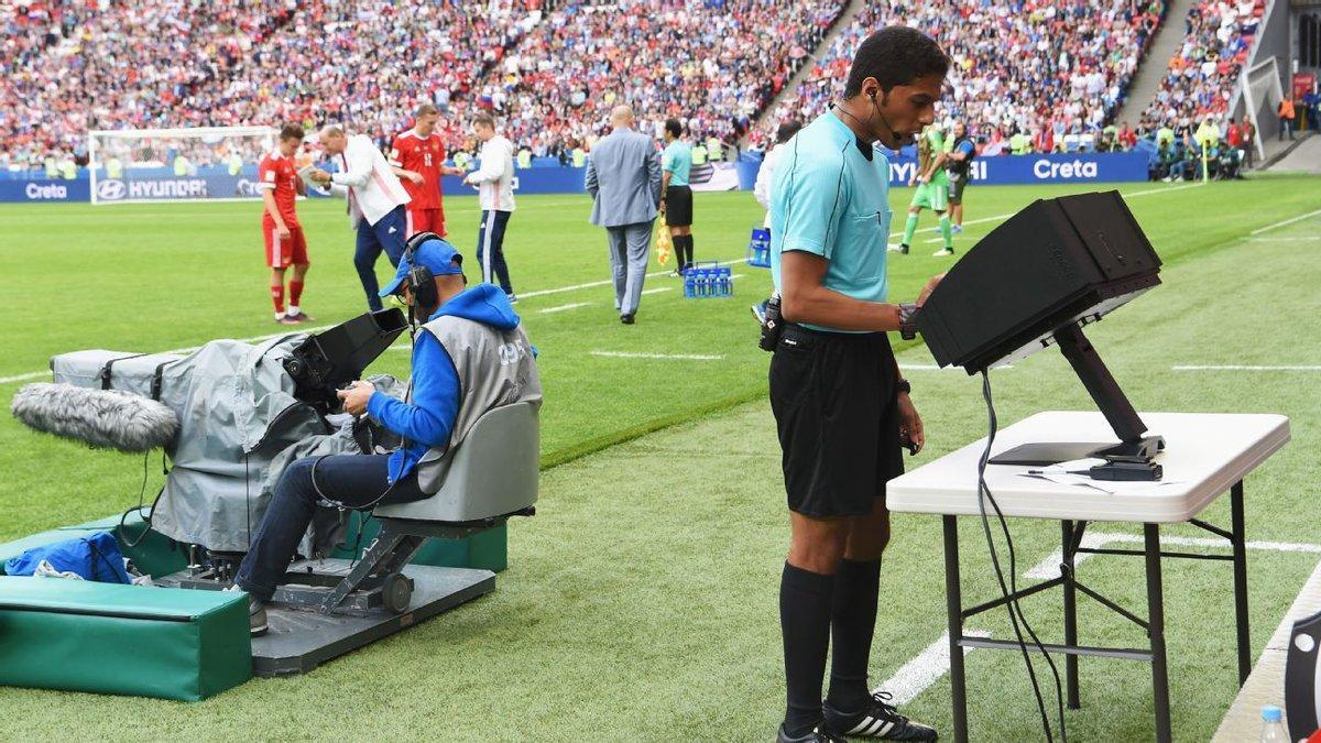 A referee uses VAR to make a call during a game.
