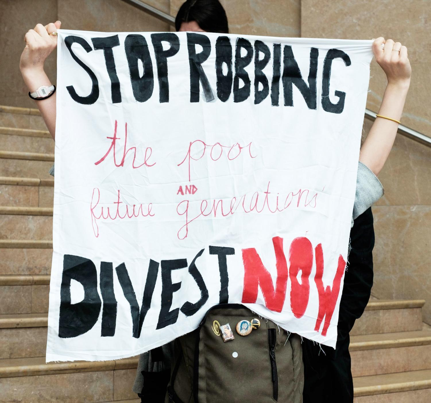 A demonstrator holds a banner that demands NYU to terminate all investments in fossil fuel companies.