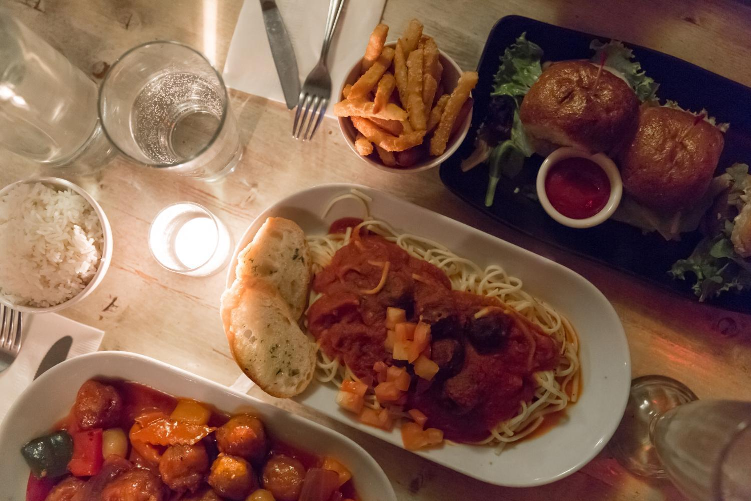 Sweet and sour chicken with white rice, spaghetti and meatballs with garlic toast, and sausage sliders with French fries.