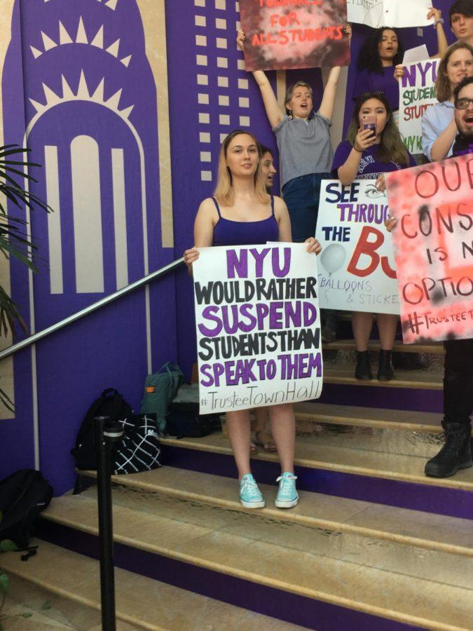 On+the+steps+inside+the+Kimmel+Center+for+University+Life%2C+a+student+activist+holds+a+sign+that+reads%2C+%22NYU+would+rather+suspend+students+than+speak+to+them+%23TrusteeTownHall.%22
