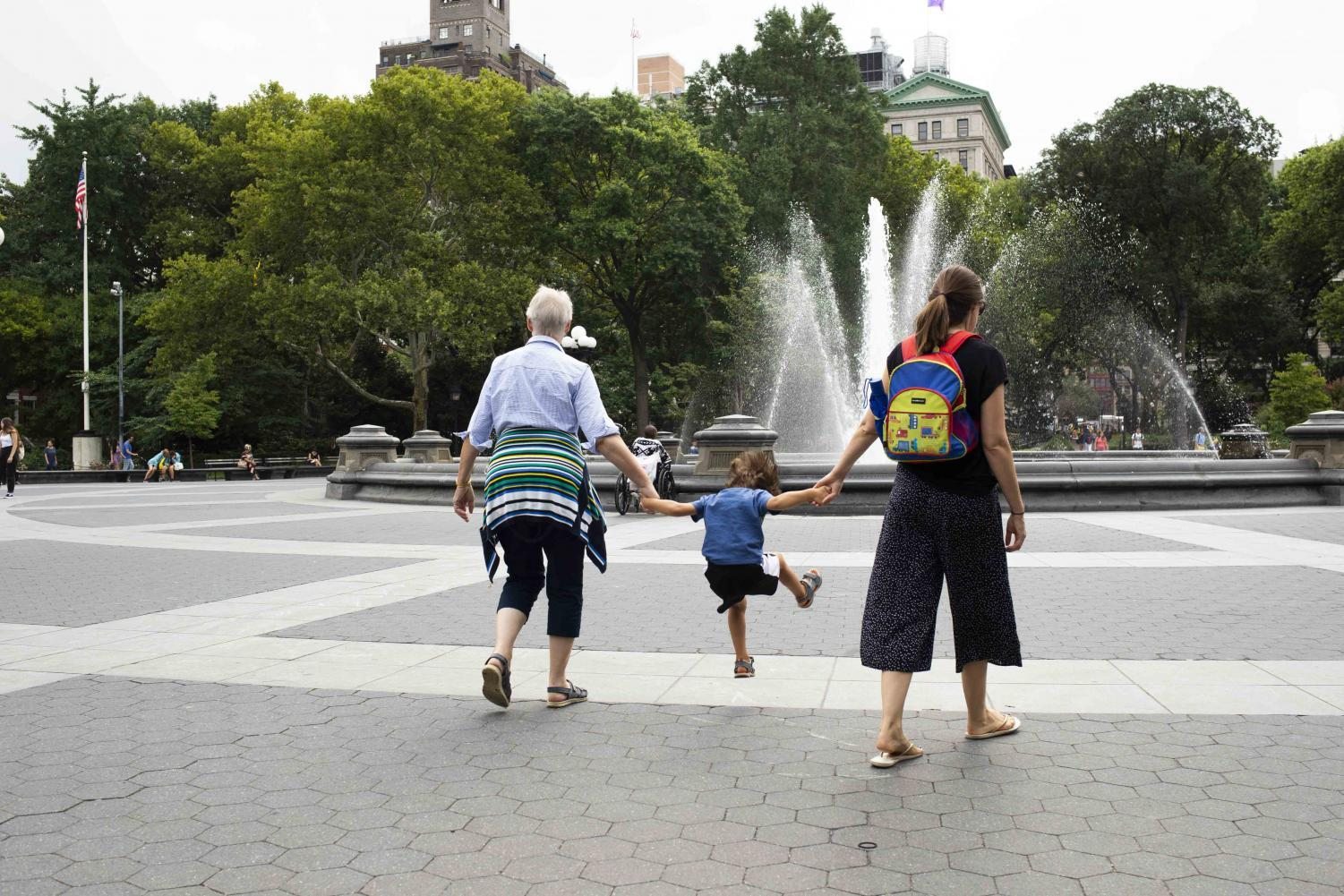 A boy jumps while holding his two guardians' hands in Washington Square Park, the location .